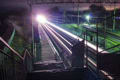 Railway station at night with a passing train Royalty Free Stock Photo