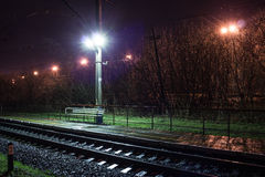 Railway station at night with a passing train Royalty Free Stock Image
