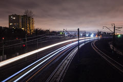 Railway station at night with a passing train Stock Image