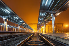 Railway station at night. Train platform in fog. Railroad Royalty Free Stock Photography
