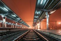 Railway station at night. Train platform in fog. Railroad Stock Images