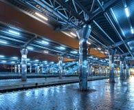 Railway station at night. Train platform in fog. Railroad Stock Photo