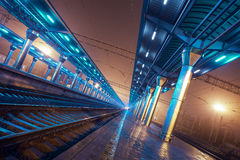 Railway station at night. Train platform in fog. Railroad Stock Photography