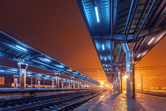Railway station at night. Train platform in fog. Railroad Royalty Free Stock Image