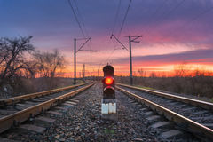 Railway station with semaphore against beautiful sky at sunset Stock Photos