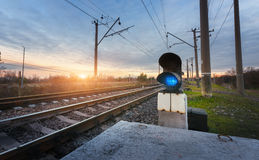 Railway station with semaphore against beautiful sky at sunset Stock Photo