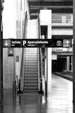 Railway station with signposting and escalators. Black and white royalty free stock photo