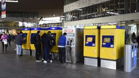 At the Railway Station Ticket Machine. Rotterdam, The Netherlands - March 10, 2017: Travelers getting their tickets at the ticket machine  in the railway station stock video footage