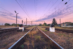 Railway station and traffic light at colorful sunset. Railroad. Railway station and traffic light at colorful purple sunset. Railroad Royalty Free Stock Image