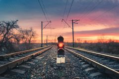 Railway station with traffic light at sunset. Railway station with semaphore against sunny sky with clouds at sunset. Colorful industrial landscape. Railroad Royalty Free Stock Photography