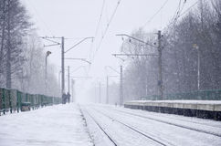 Railway station in the winter snowstorm. Empty railway station in heavy snowfall with thick fog. Railway rails go away in a white fog of snow. The concept of the Stock Photography