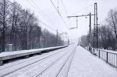 Railway station in the winter snowstorm. Empty railway station in heavy snowfall with thick fog. Railway rails go away in a white fog of snow. The concept of the Stock Photos