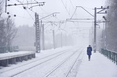 Railway station in the winter snowstorm. Empty railway station in heavy snowfall with thick fog. Railway rails go away in a white fog of snow. The concept of the Stock Image