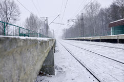 Railway station in the winter snowstorm. Empty railway station in heavy snowfall with thick fog. Railway rails go away in a white fog of snow. The concept of the Stock Photo