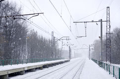 Railway station in the winter snowstorm. Empty railway station in heavy snowfall with thick fog. Railway rails go away in a white fog of snow. The concept of the Royalty Free Stock Photo