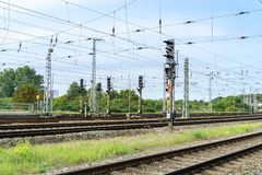 Railway system with power lines and traffic lights. Day, sunny, gras, blue, green Royalty Free Stock Photography