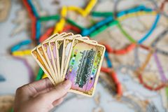 Hand hold cards of Ticket to ride game. stock photos