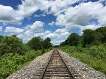 Railway to horizon and clouds on the sky background. Royalty Free Stock Photos