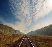 Railway to horizon in forest on autumn under clouds Stock Photo