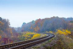 The railway track among colorful trees in the fall_ stock image