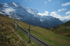 Railway track connecting Kleine Scheidegg and Jungfraujoch (Bernese Alps, Switzerland). The Kleine Scheidegg is a mountain pass (2,061 metre), situated below and Royalty Free Stock Photo
