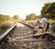 Railway track crossing rural landscape with travel backpack Stock Photo