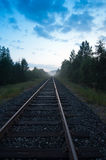 Railway track in the evening. Railway track leading towards the center. Blue evening sky on the top and hint of fog in the horizon stock photos