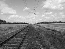 Railway track through fields Royalty Free Stock Images
