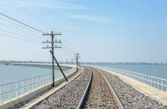 Railway track lead across the lake Stock Photos
