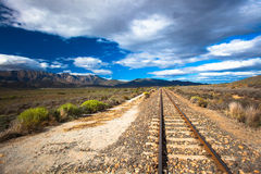 Railway Track Mountains Landscape. Railway line goes straight into the distance with the mountains with coming rain clouds at days end on the left hand side of Stock Photography