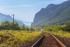 Railway track in the mountains. Serene landscape with rusty railway track passing through Cozia mountains along Olt river gorge in Valcea county, Romania Stock Image