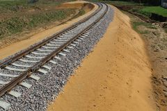 Railway track: rails, sleepers laid through fields, forests for transportation of goods and people. The railway is built of sleepers and rails.Wooden sleepers stock photo