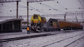 Railway track snow removal machine. Railway track snowplow runs through the railway cleans the snow drips away the ice at the station rails contact wires posts stock video footage