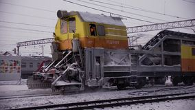 Railway track snow removal machine. Railway track snowplow runs through the railway cleans the snow drips away the ice at the station rails contact wires posts stock video