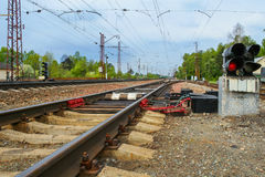 Railroad switch and traffic light. Railway track stretching into the distance, in the foreground a red traffic light and switch Royalty Free Stock Images