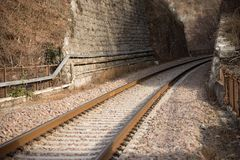 Railway track towards a gallery. Alpine section of a single-track railway track in Italy, Trento Royalty Free Stock Image