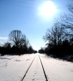 Railway track in winter. Scenic view of snow covered railway track in countryside under shining sun Stock Images