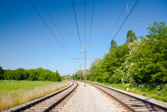 Railway tracks. Two railway tracks on gravel with electric cables royalty free stock images