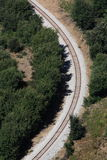 Railway tracks bend. A section of stone-supported railway tracks runs in a bend, surrounded by trees royalty free stock photos
