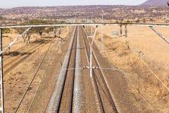 Railway Tracks Dry Landscape. Railway train tracks line travel through dry season rural landscape Stock Photo