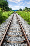 Railway tracks with green grass, mountain and blue sky, Thailand. Royalty Free Stock Photos