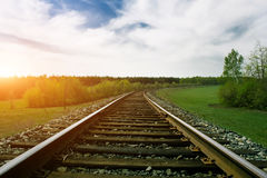 Railway tracks on green summer landscape at sunset Stock Photos