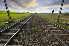 Railway tracks into horizon. Dual railway tracks stretching into horizon, dramatic clouds and sky Royalty Free Stock Image
