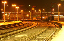 Railway tracks in the night. Railway tracks in the darkness, orange light, in the background a train Stock Photos