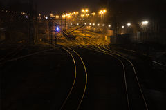 Railway tracks at night lead shiny and curving to a cargo freigh Royalty Free Stock Photo