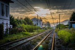 Railway tracks with old buildings on sides, wires above and Tuscany hills and mountains with dramatic cloudy sky background royalty free stock photography