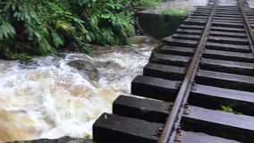 Railway above river. Railway tracks pass above powerful water stream in tropical forest stock video footage