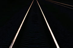 Railway tracks in the shadow light of sunset. Royalty Free Stock Images