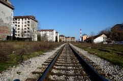 Railway tracks weathered apartment buildings and red industrial chimney Belgrade Serbia. Belgrade, Serbia - March 20, 2015: A section of Belgrade city divided by Royalty Free Stock Photography