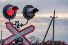 Railway traffic light. Railway red traffic light and crossing sign on sky background Royalty Free Stock Photography